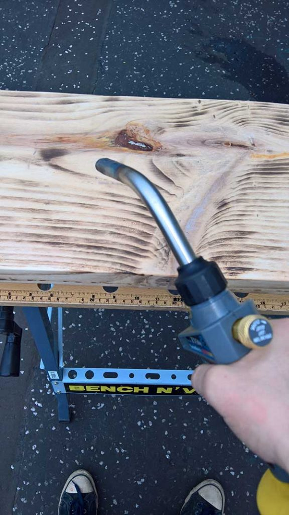 using a blowtorch to scorch timber